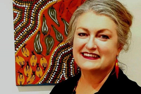 Associate Professor Michelle Dickson smiles and stands in front of a painting.