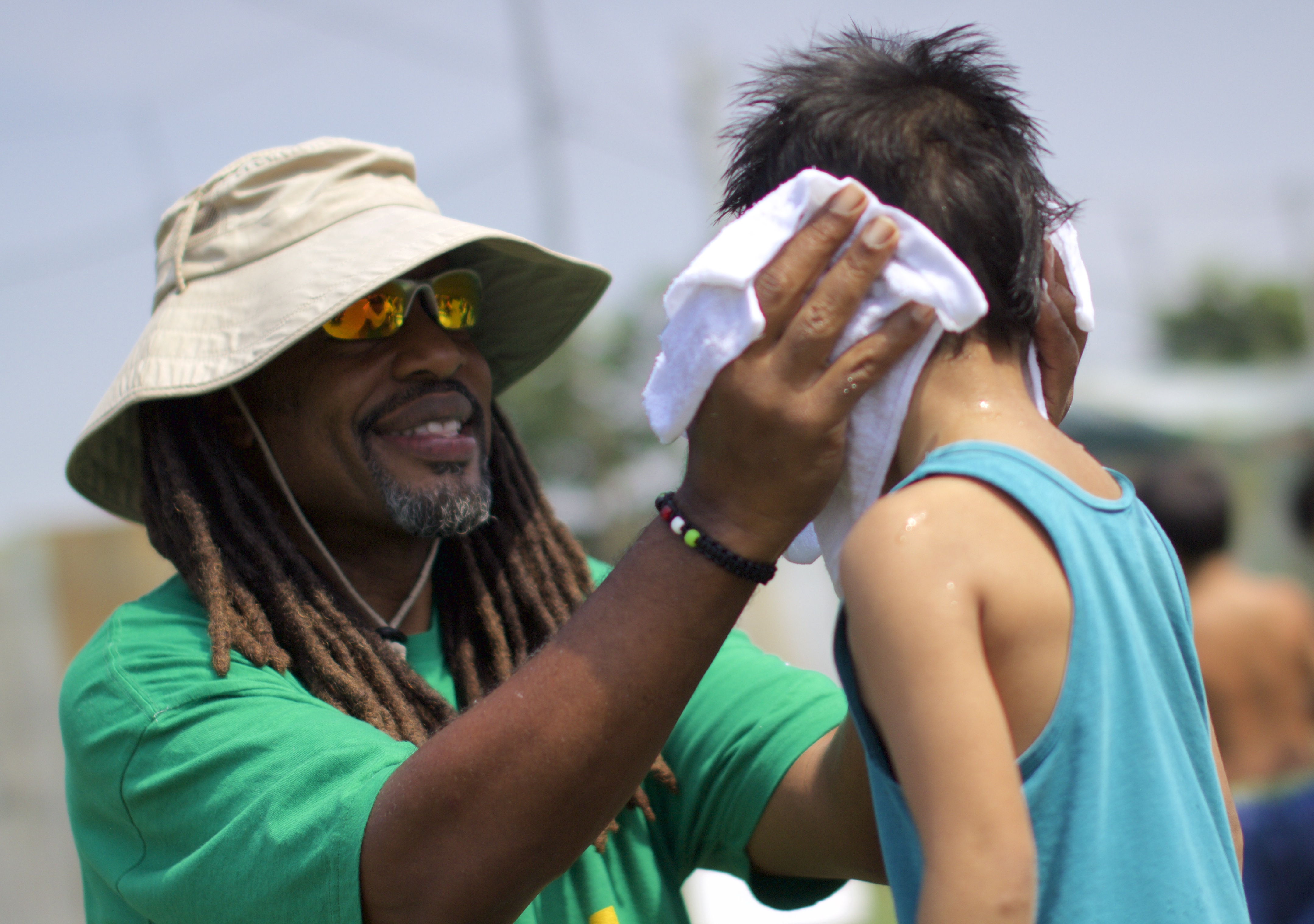 A man in a hat and dreadlocks smiles as he dries the hair of a small boy. Credit John Christian Fjellestad, Flickr.