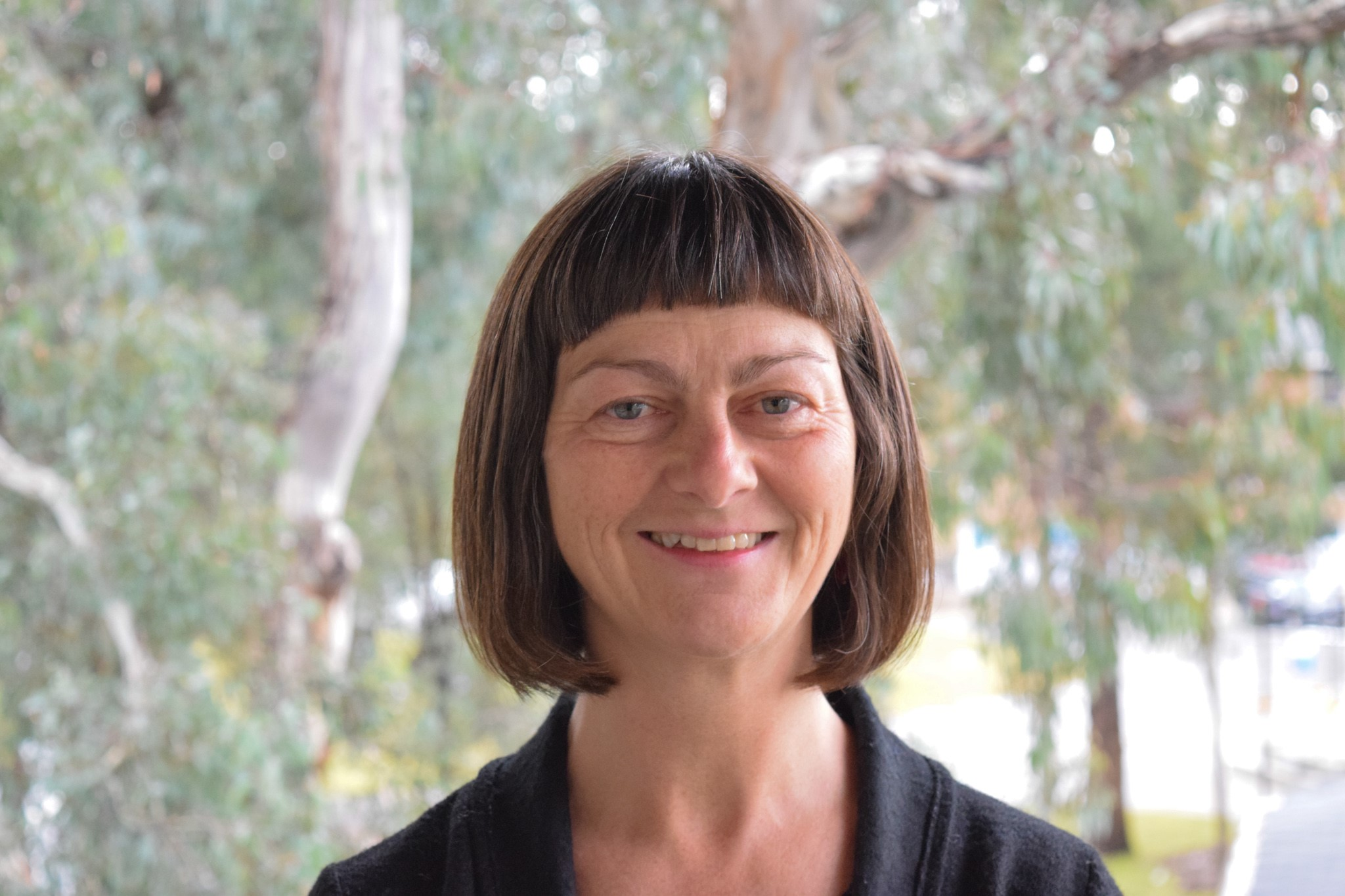 Professor Sharon Friel smiles and looks at the camera. The background features trees.