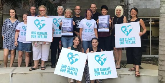 """Participants at a Climate and Health Alliance workshop in Townsville stand outside and hold signs which read """"our climate, our health"""" and also """"prevention is better than cure."""""""