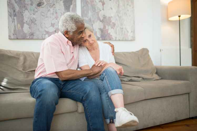 elderly couple embracing while sitting on a sofa