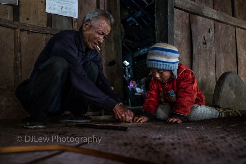 Ahka family. Grandfather & grandson repairing bamboo thatch, mother inside watch satellite TV