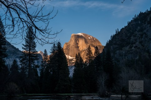 Sunset along side the Merced River where the majestic Half Dome grabs the last bit of light for the day, glowing orange that matches the suns warm before the cool night ahead