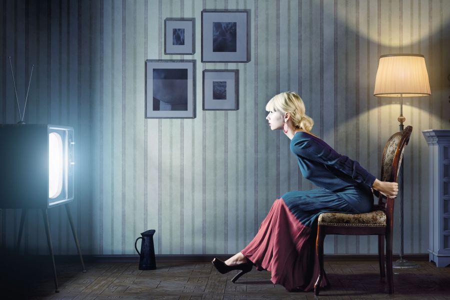 Девушка сидит перед телевизором
