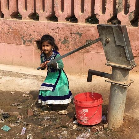 Una bimba indiana raccoglie acqua in un pozzo