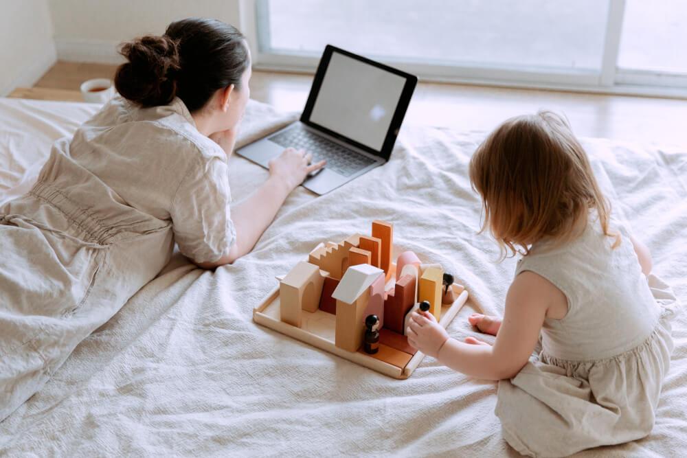 vrouw op bed met laptop en kindje ernaast aan het spelen - introvert zijn en ouderschap