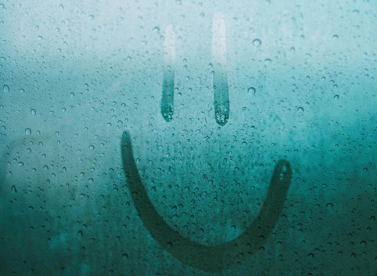 op een beslagen raam is een smiley getekend