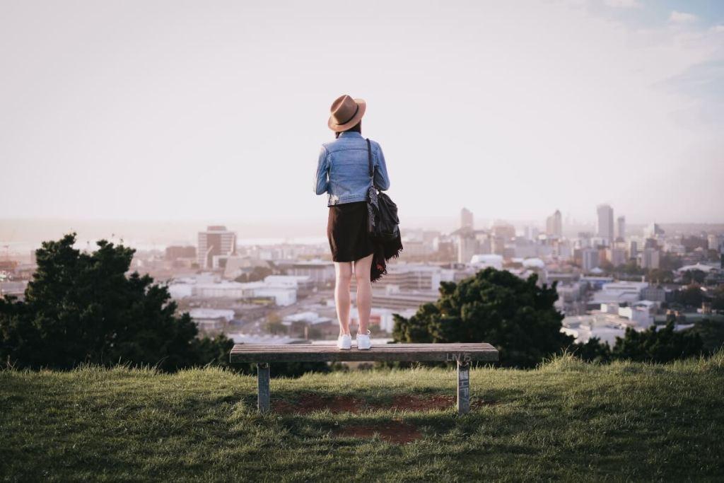 persoon staat op een bankje om nog beter over de stad uit te kunnen kijken