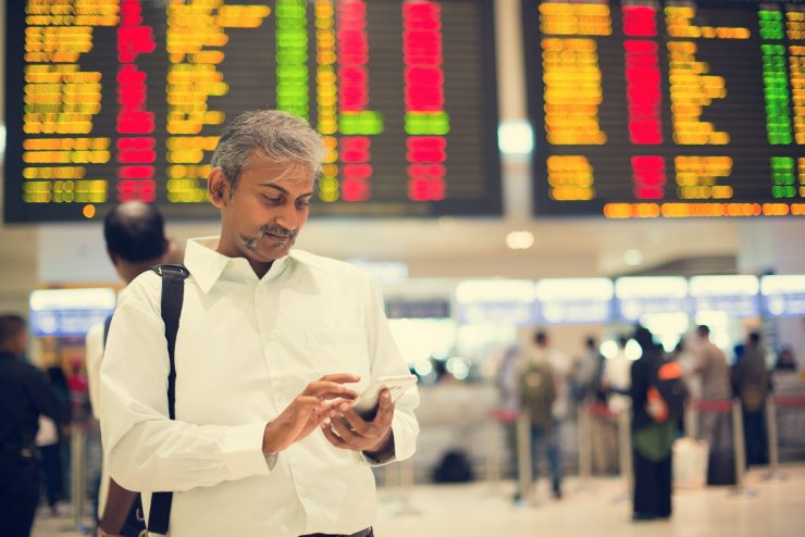 An Indian man checking his phone in an airport