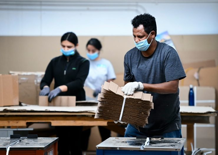 Workers manufacture cardboard petitions.