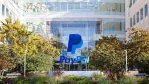 Logo PayPal (PYPL) prekrýva fotografiu podnikovej budovy za denného svetla