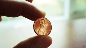 Immagine di un penny tenuto tra due dita con uno sfondo bianco per interni