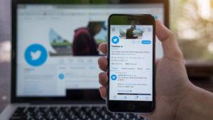 Aplikácia Twitter (TWTR) sa zobrazuje na obrazovke telefónu držanej v ruke človeka.