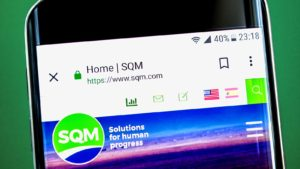 Sociedad Quimica y Minera (SQM) logo displayed on a mobile phone with the company's web page on it