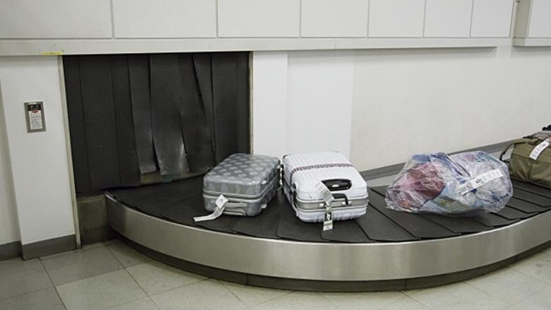 空港ターンテーブルでスーツケース受け取り