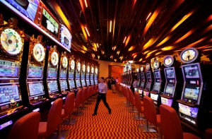An attendant walks between rows of slot machines inside the Resorts World Sentosa casino on Singapore's Sentosa Island
