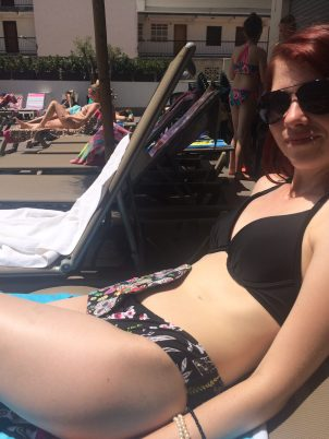 A photo of me reclining on a lounger in my bikini, with the stoma bag just visible to the right hand side of my tummy.