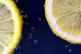 A close up photo of two lemon slices with bubbles around as though they're under water. The background is dark blue.