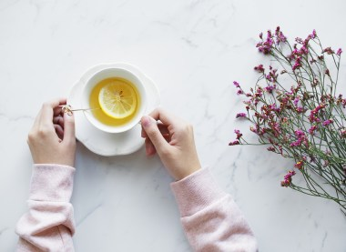 A birds eye view of a woman with her hands on her cup of hot lemon tea. It's sat on a white table and some purple flowers are lying to the right.
