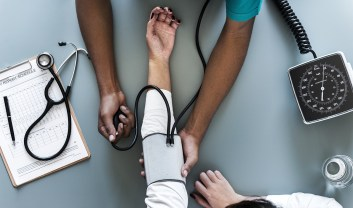 A birds eye view of a grey table with a medical chart on it and a patient's arm stretched out as the doctor inflates a blood pressure cuff.