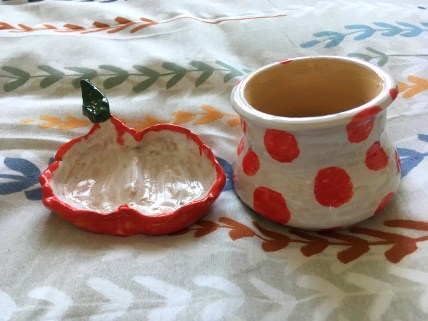 A photo of the pottery I made on my beed. One is like a half apple, created as a dish. The other is a small pot in white with red polka dots.