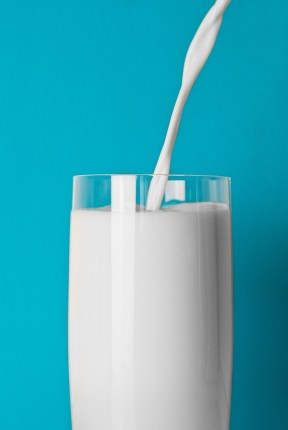 A blue background with a close up of a glass of milk, with milk being poured in from above.