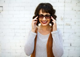 A woman backdropped by a white brick wall. She's smiling and wearing black migraine glasses, with her hands up as though massaging her temples.