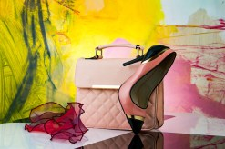 An expensive-looking handbag and shoe against a colourful background.