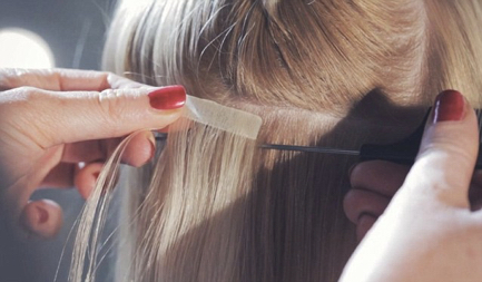 A close-up of someone's blonde hair as an extension is being taped in.