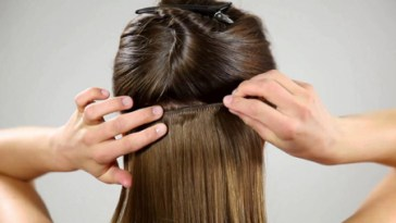 The back of a brunette's head as she reaches her hands to her hair and places in a hair extension.