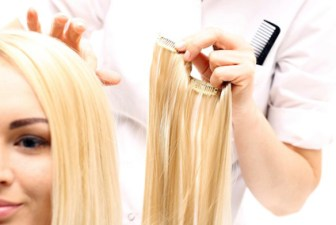 A woman's face as a lady behind her holds up a hair extension ready to clip into her blonde hair.