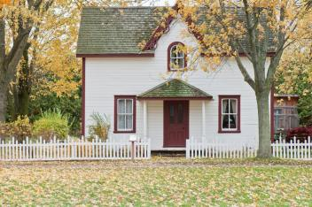 Photo of a house with a white picket fence and grass out front.