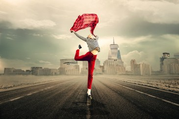 A woman standing on a road with a city scape behind her. She's stretching and holding a top above her head, as though she's free and feeling liberated.