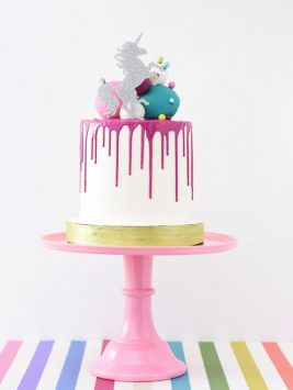 Photo of a cake on a stand, which is on a rainbow striped tabled. The cake is large with pink icing, and a silver unicorn on top.