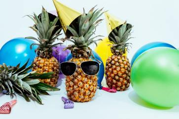 Photo of pineapples having a party, wearing sunglasses and party hats, surrounded by balloons.