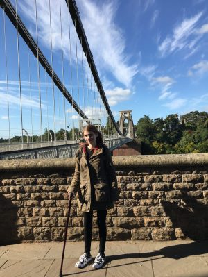 A photo of me at one side of the Clifton Suspension Bridge in Bristol. It's a blue cloudy sky with the bridge stretching out behind me. I'm wearing a big green coat as it's cold, and I've got a walking stick.