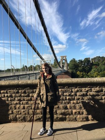 A photograph of me in a winter coat despite the bright weather, with a walking stick in my right hand.  I'm next to a short wall and the bridge spans out behind me, against a blue sky with light clouds.
