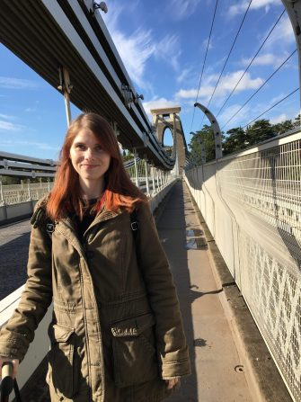A photo of me part way across the bridge, standing on the pedestrian walkway with the sky above (blue with light clouds) and the railings to either side.