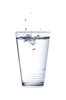 A photo of a glass of water with a splash forming from being filled up.
