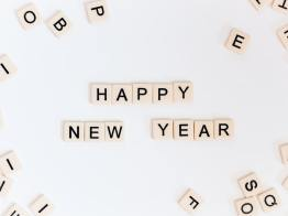 """Happy New Year"" is written is scrabble tiles against a white background."