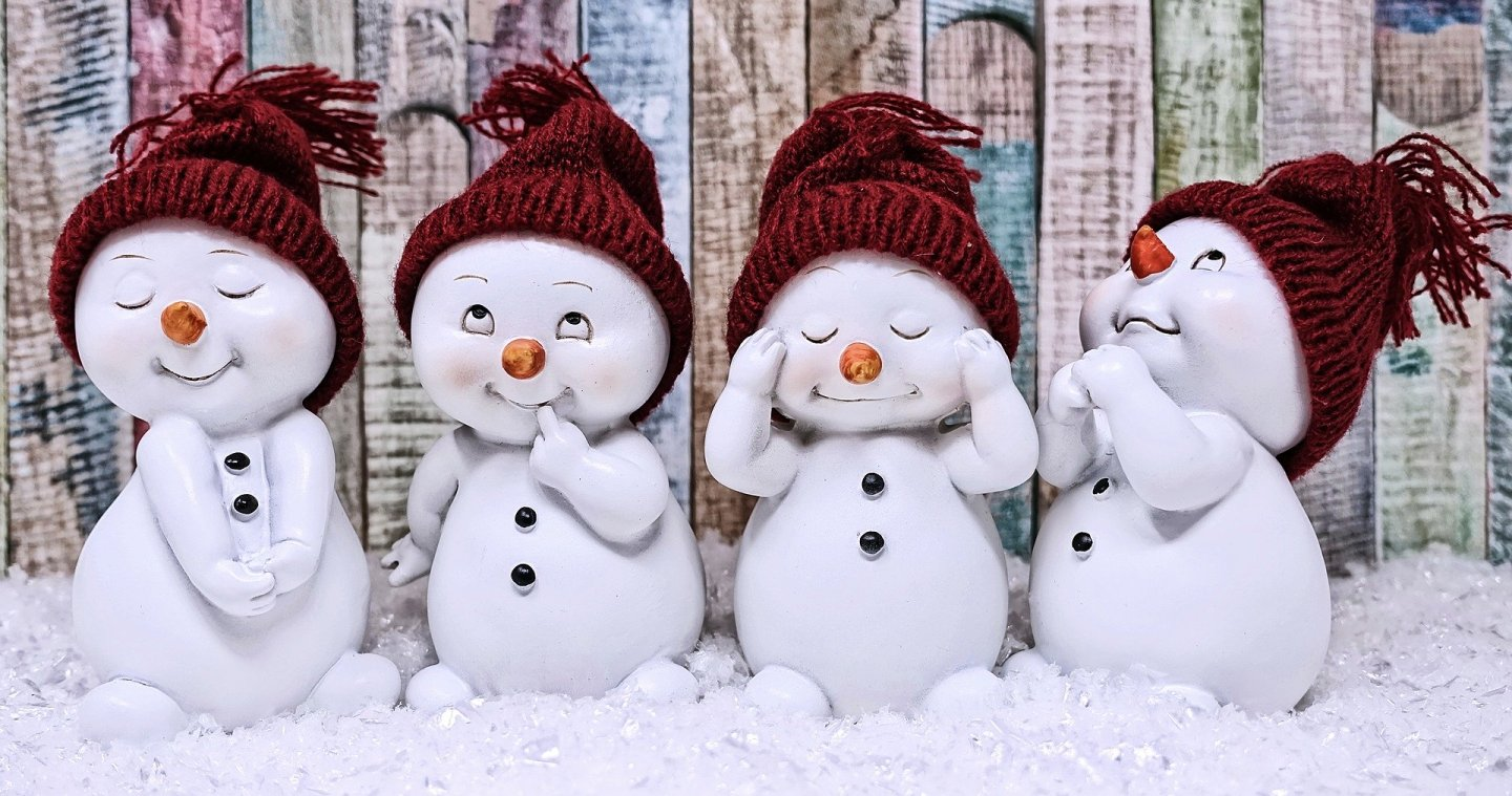 Four cartoon style toy snowmen with hats and cute smiles, all wearing hats. They're in pretend snow against a coloured wooden fence.