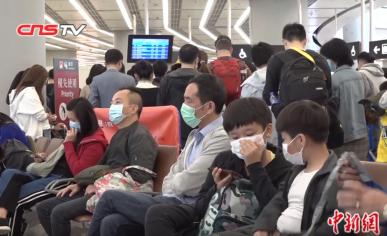 A photo of many people in an airport in China wearing face masks, with the CNSTV logo at the top as this is a Wikipedia Commons image taken from a media broadcast.