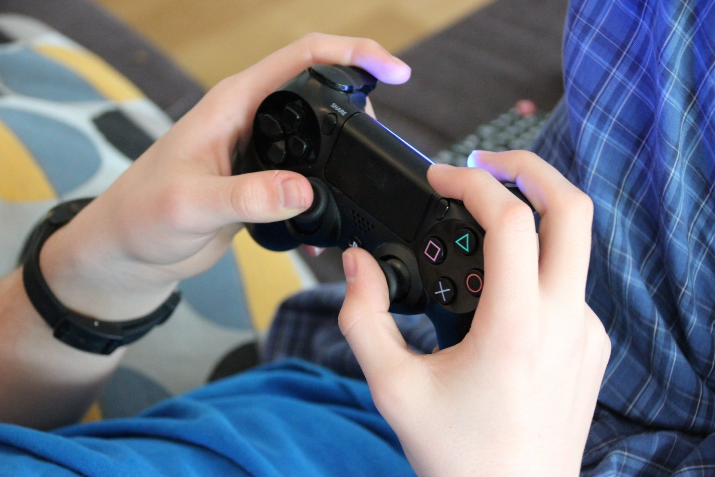 A photo of a child's hands holding a Playstation game controller as he plays a game.