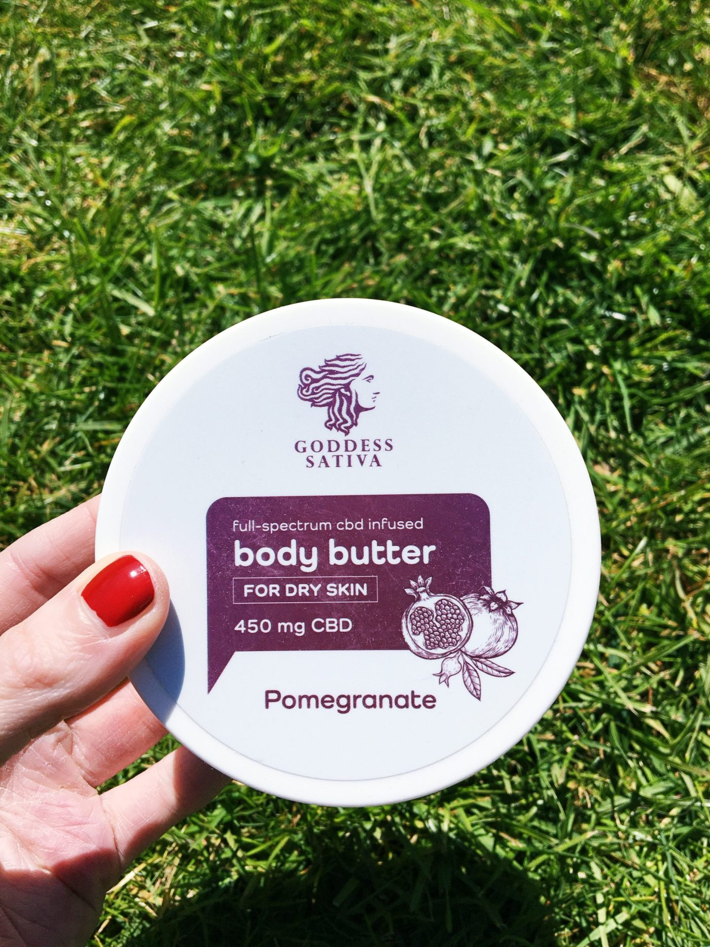 Me holding the body butter. It's a disc-shape tub in white. On the lid is the label in shiny pink. I'm holding the tub and I'm wearing red nail varnish, with the grass in my garden as the background.