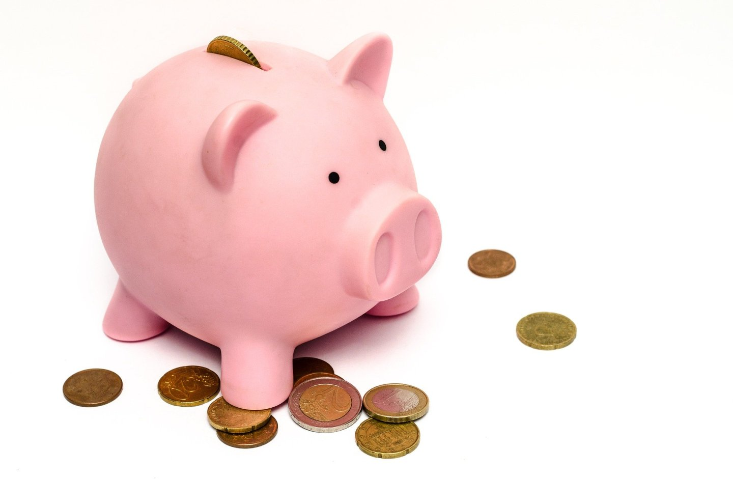 A pink piggybank with a totally white background, with a few coins spread around it.