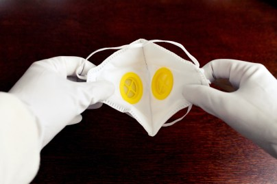 Gloved hands opening a fold-flat respirator mask to show the inside of two valves.