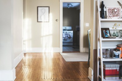 The interior of a hallway in a home showing hardwood floors, light coloured walls, a shelf with ornaments to the right and a door into another room ahead.