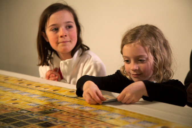 a_girl_helps_lay_down_the_final_cards