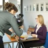 Filmemacherin Alicia-Eva Rost überprüft das Bild, eine blonde Frau sitzt an ihrem Arbeitsplatz, ein Dreh von InZwischenZeit
