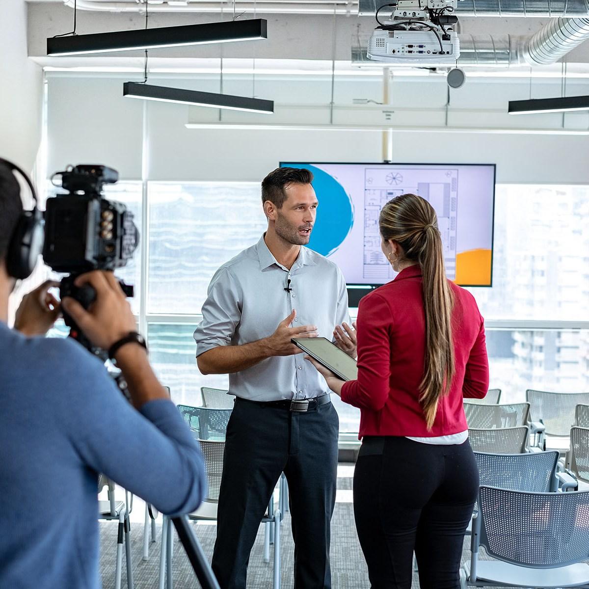 Overshoulder eines Interviews, Dreh einer Videobotschaft. Ein Kameramann in einem blauen Pullover filmt zwei Personen, die ein Interview in einem Loft führen.